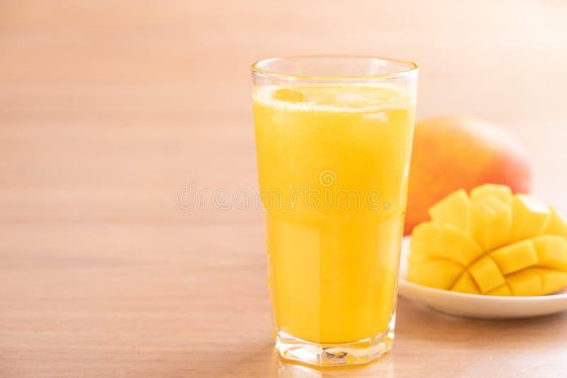 Świeży mangowy sok z pięknymi siekającymi miąższowymi ciałami i słomą na jaskrawym drewnianym stołowym tle Tropikalnej owoc proje fotografia stock
