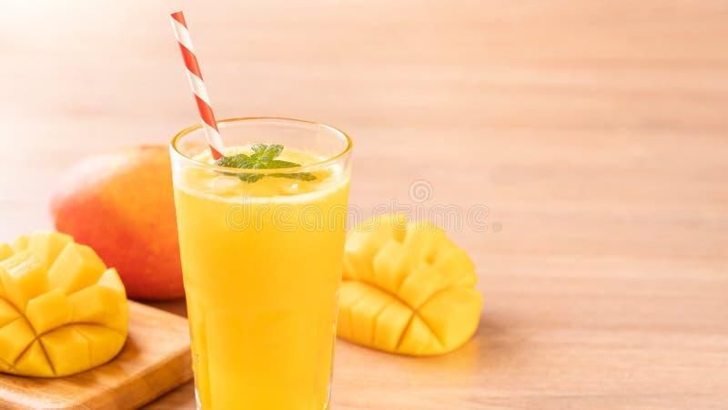 Świeży mangowy sok z pięknymi siekającymi miąższowymi ciałami i słomą na jaskrawym drewnianym stołowym tle Tropikalnej owoc proje obrazy royalty free
