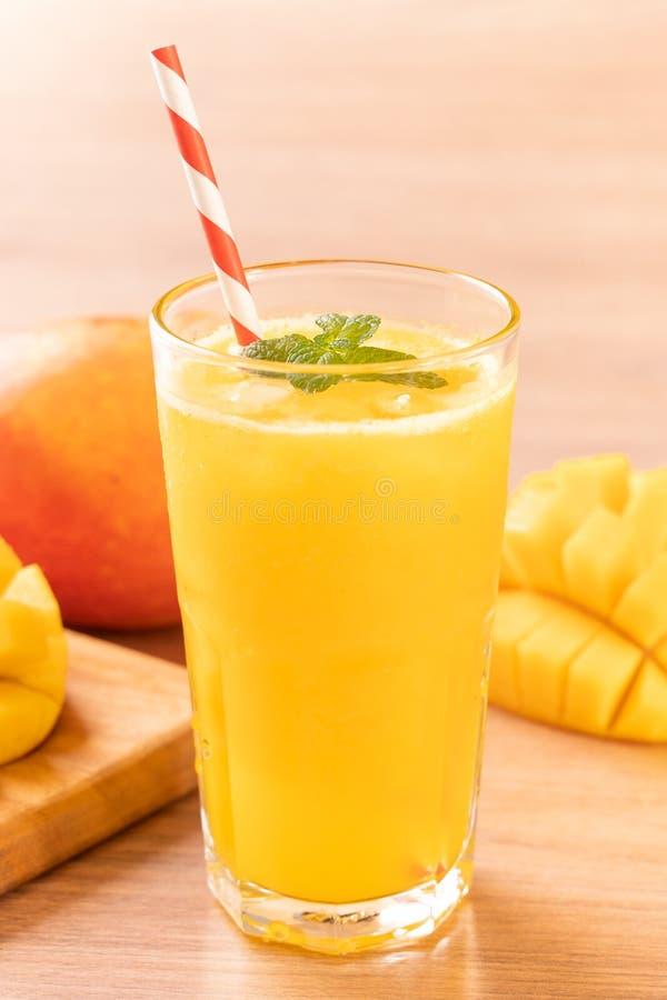 Świeży mangowy sok z pięknymi siekającymi miąższowymi ciałami i słomą na jaskrawym drewnianym stołowym tle Tropikalnej owoc proje zdjęcia stock
