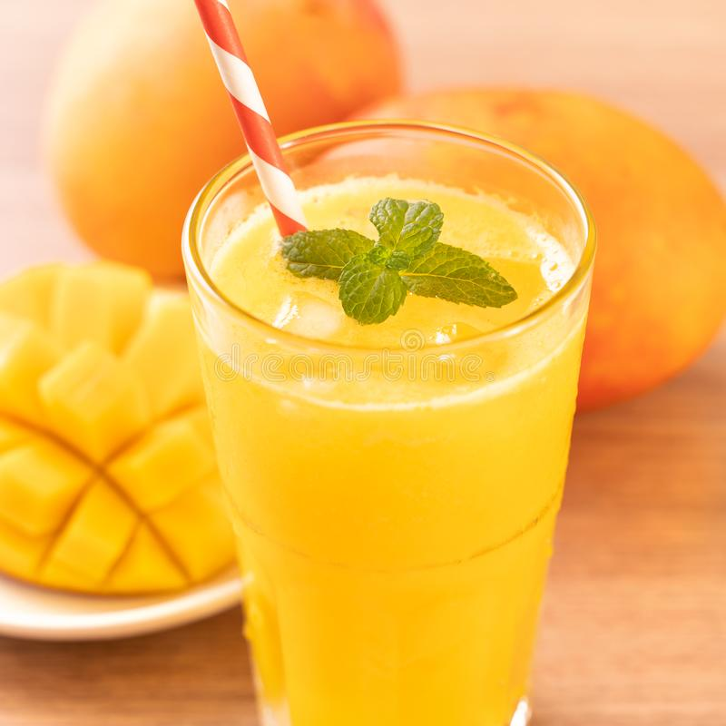 Świeży mangowy sok z pięknymi siekającymi miąższowymi ciałami i słomą na jaskrawym drewnianym stołowym tle Tropikalnej owoc proje obraz royalty free