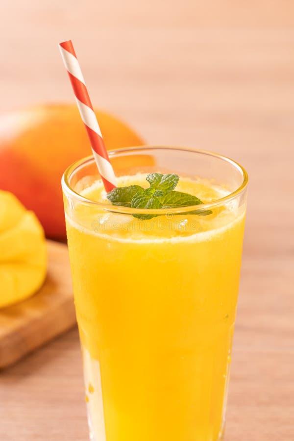 Świeży mangowy sok z pięknymi siekającymi miąższowymi ciałami i słomą na jaskrawym drewnianym stołowym tle Tropikalnej owoc proje obraz stock