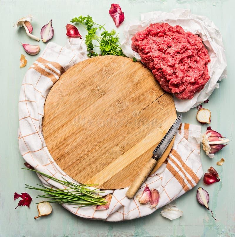 Świeży minced mięso z świeżymi ziele i pikantność wokoło drewnianej tnącej deski zdjęcie stock