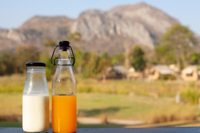 Świeży mleko i sok pomarańczowy w butelkach stawiać wraz z widokiem górskim jako tło obrazy royalty free