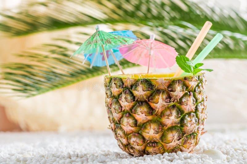 Świeży napój w ananasie na piaskowatej plaży zdjęcie stock