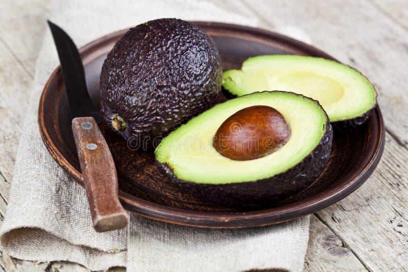 Świeży organicznie avocado na ceramicznym talerzu i nożu na bieliźnianej pielusze na nieociosanym drewnianym stołowym tle obrazy royalty free
