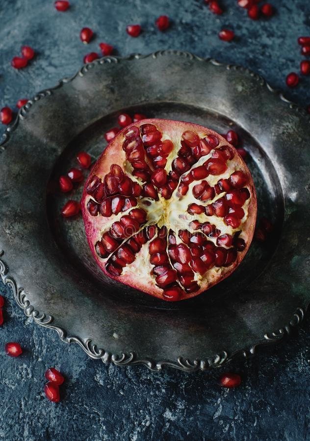 Świeży organicznie soczysty granatowiec na srebnym talerzu na zmroku kamienia tle fotografia stock