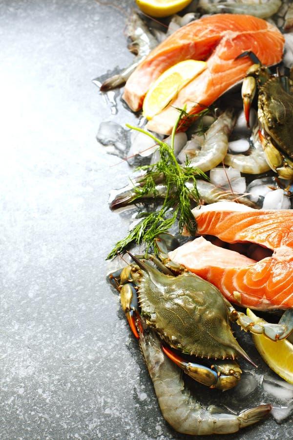 Świeży owoce morza: łososiowy stek, kraby i garnele na kamiennym tle, obraz royalty free