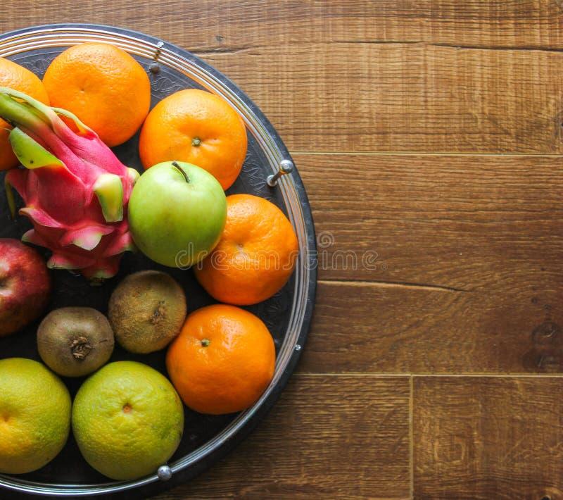 Świeży owocowy kosz zawiera smok owoc, jabłka, kiwi, pomarańcze, bonkrety na drewnianym tle fotografia stock