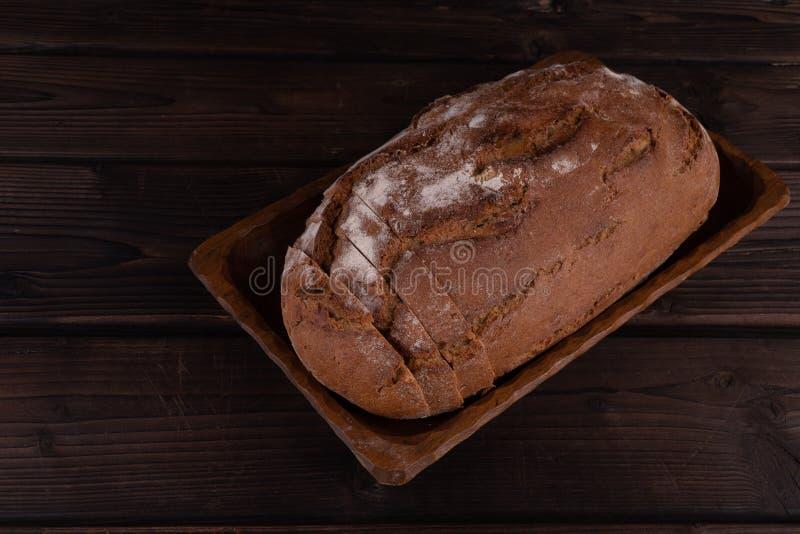 Świeży piec pokrojony chleb na nieociosanym drewnianym stole fotografia stock