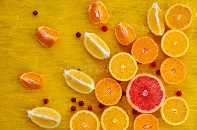 Świeży pokrojony grapefruitowy, pomarańczowy, cytryny, tangerines i czerwieni cranberries na drewnianym stole, Składniki dla soku obrazy stock