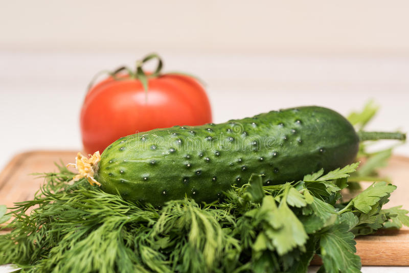 Świeży pomidor, ogórek, pietruszka i koper na tnącej desce, obrazy stock