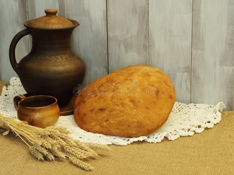 Świeży rumiany chleb, earthenware dzbanek i filiżanka z ucho, banatka na białej pielusze i jutowa kanwa przeciw tłu naturalny dre zdjęcie royalty free