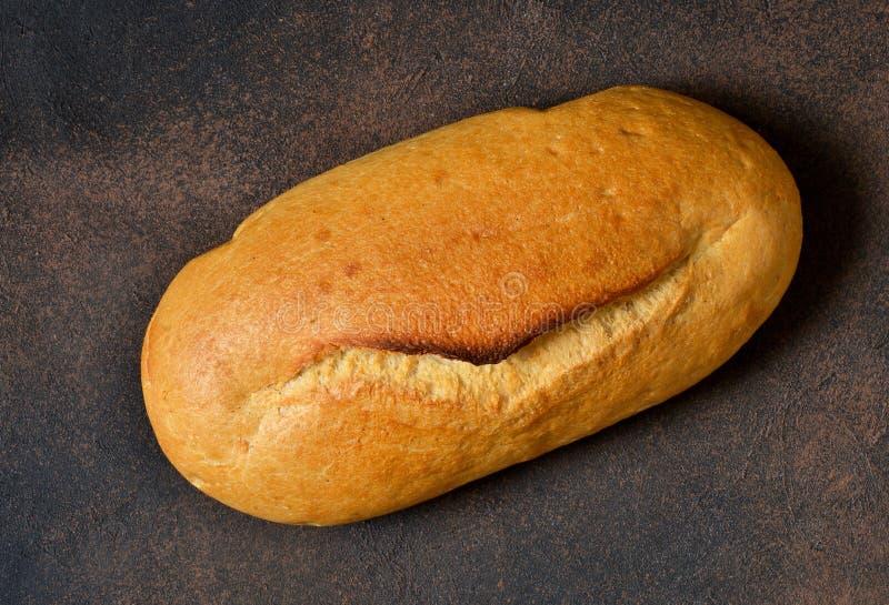 Świeży, rumiany pszeniczny chleb na betonowym tle, obraz royalty free