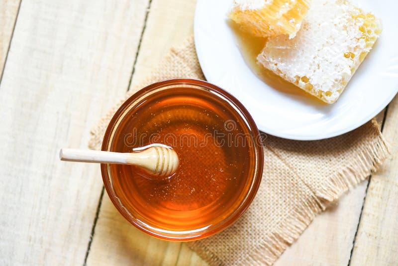 Świeży słodki miodowy słój z drewnianą chochlą i honeycomb na bielu talerzu na drewnie zgłaszamy tło obraz stock