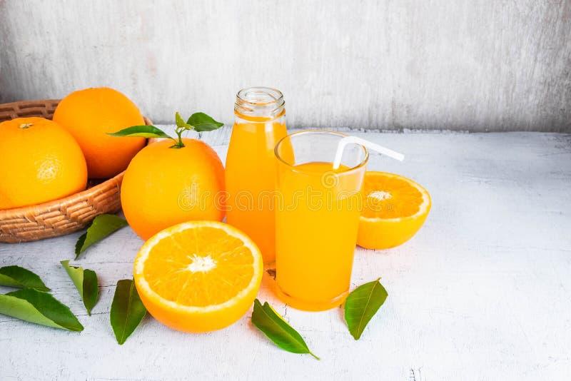 Świeży sok pomarańczowy i pomarańcze w koszu na białym drewnianym bac zdjęcia stock