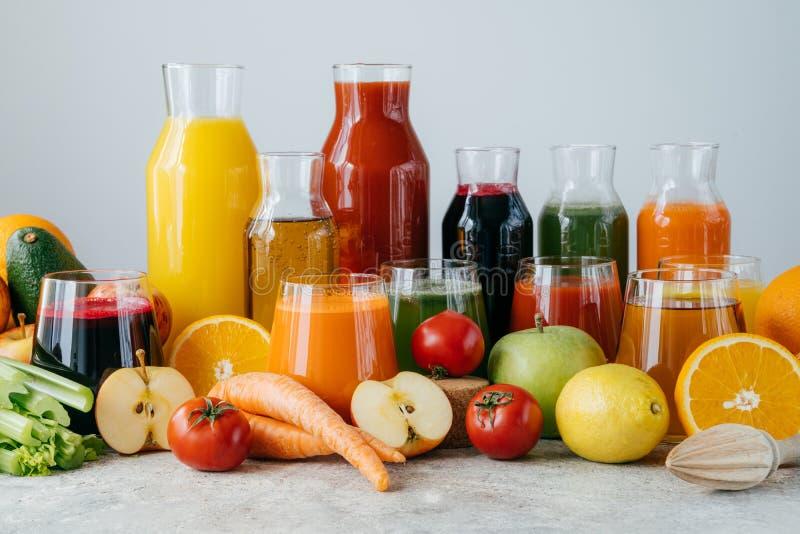Świeży sok robić różnorodni warzywa i owoc w szklanych słojach na popielatym stole, odosobniony nadmierny biały tło ?wie?o gnios? obrazy royalty free