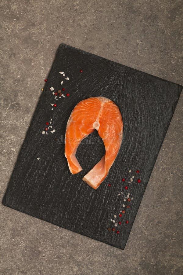 Świeży Surowy Łososiowy Czerwony Rybi stek na czarnym łupku talerzu zdjęcie royalty free