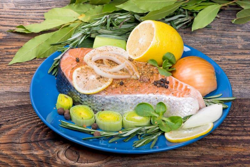 Świeży surowy łososiowy czerwony rybi stek z ziele i warzywami zdjęcia stock