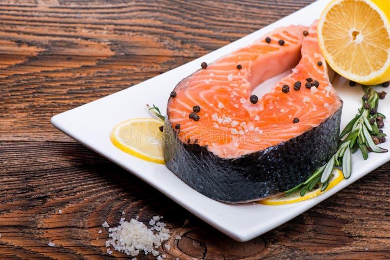 Świeży surowy łososiowy czerwony rybi stek z ziele, pikantność zdjęcia stock