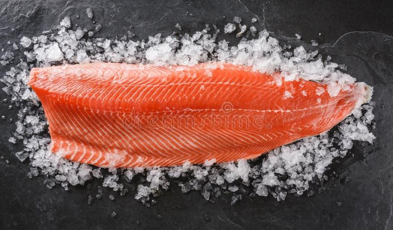 Świeży surowy łososiowy rybi stek z pikantność na lodzie nad zmroku kamienia tłem zdjęcie stock