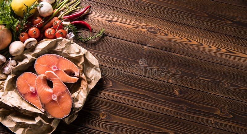 Świeży surowy łososiowy rybi stek z ziele i warzywami zdjęcia royalty free