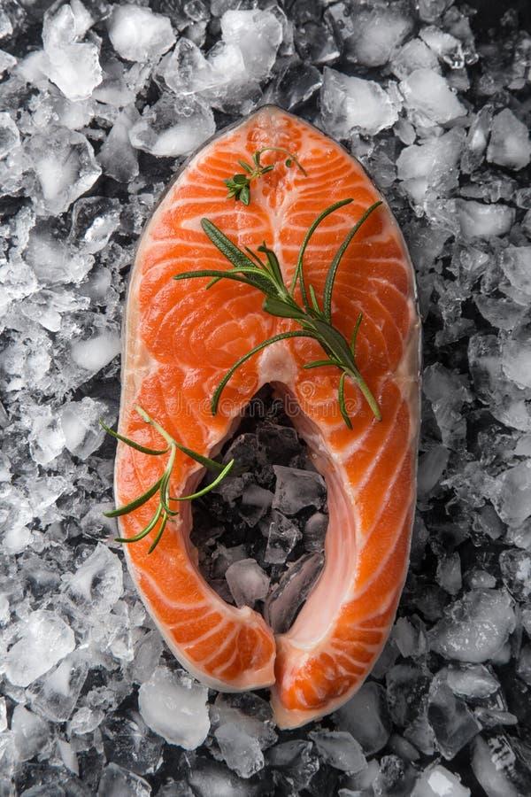 Świeży surowy łososiowy stek z macierzanką i rozmarynami na lodzie fotografia royalty free