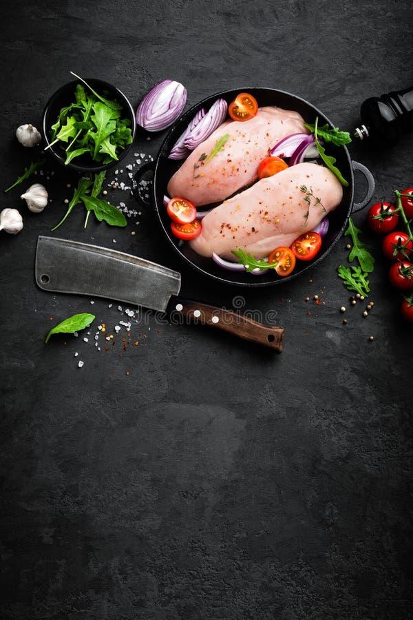 Świeży surowy kurczaka mięso, przepasuje marynowanego z pikantność, cebulą i pomidorami na czarnym tle, fotografia royalty free