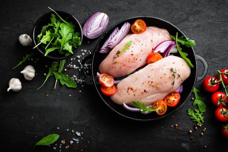 Świeży surowy kurczaka mięso, przepasuje marynowanego z pikantność, cebulą i pomidorami na czarnym tle, zdjęcie royalty free