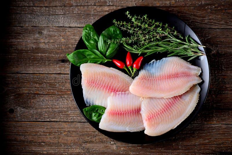 Świeży surowy polędwicowy tilapia ryba z macierzanki, rozmarynów, basilu i chili pieprzem, fotografia stock