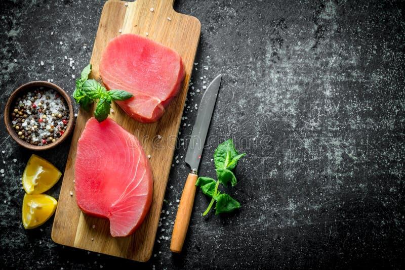 Świeży surowy tuńczyka stek na drewnianej tnącej desce z plasterkami, pikantność i mennicą cytryny, zdjęcie royalty free