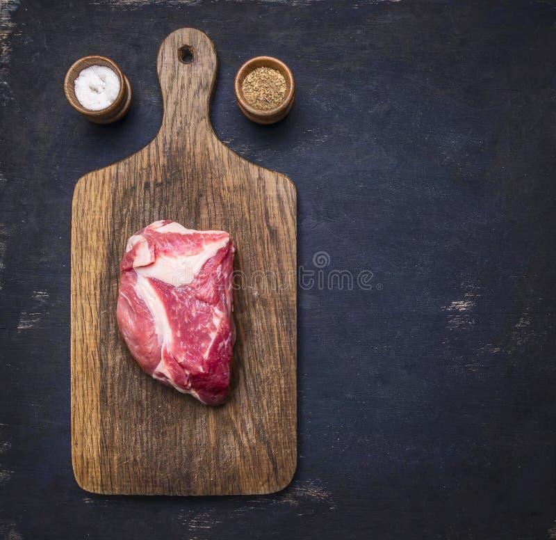 Świeży surowy wieprzowina stek na rocznik tnącej deski mięsie na ciemnym drewnianym tle z pieprzem, sól z przestrzenią dla teksta zdjęcia royalty free