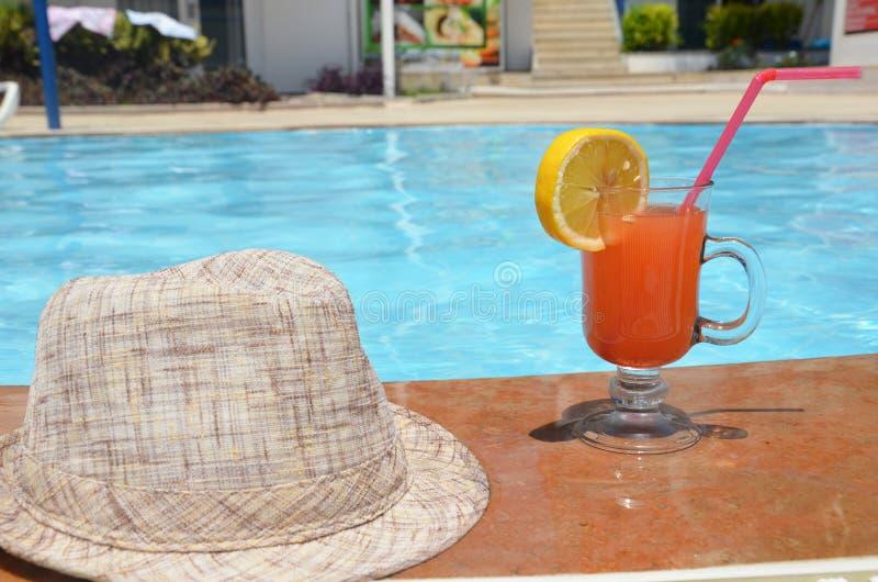 Świeży szkło melonu smoothie napój z okularami przeciwsłonecznymi, słomianym kapeluszem i kapciami na granicie pływacki basen, -  obraz stock