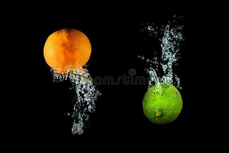 Świeży wapno i pomarańcze w wodzie z lotniczych bąbli wodą bryzgamy iso obraz royalty free