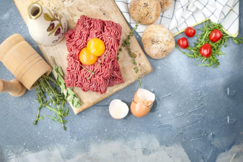 Świeży wołowiny mięso w forcemeat, na drewnianej desce Surowi jajka i pomidory są mali Ziele dla gotować i round babeczek Na szar obraz stock