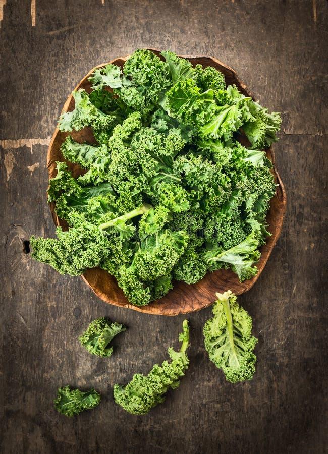 Świeży zielony kędzierzawy kale w drewnianym naczyniu na ciemnym tle zdjęcia royalty free