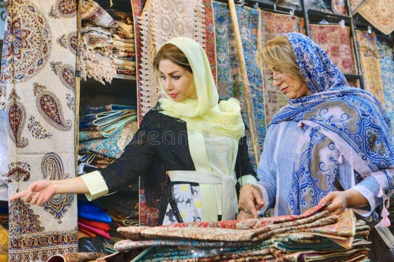 Świeckie Irańskie kobiety wybierają towary dla zakupu w dywanowym sklepie fotografia royalty free