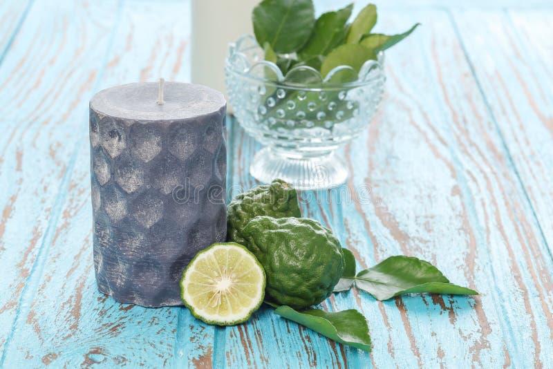 Świeczka aromata kaffir bergamotowy wapno opuszcza zielarskiego błękitnego drewnianego tek zdjęcia royalty free