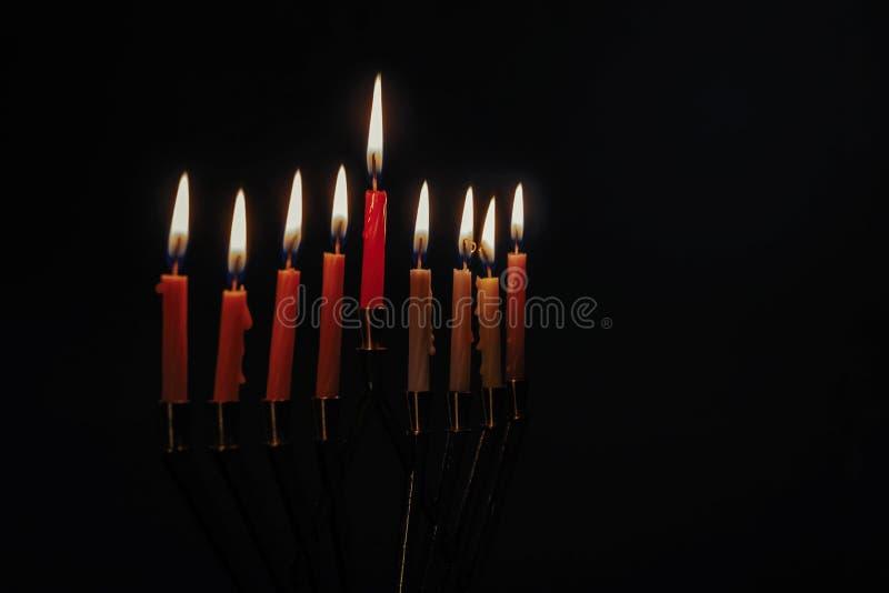 Świeczka Lite na tradycyjnym Srebnym Hanukkah menorah czerni tle zdjęcia stock