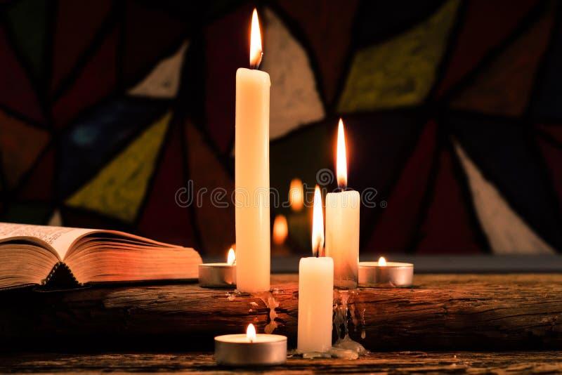 Świeczka na starym dębowym drewnianym stole Piękny witraży okno tło książkowa pojęcia krzyża religia zdjęcia stock