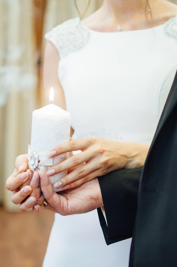 Świeczka w rękach nowożeńcy symbolizuje hearth i pomyślność rodzina obraz royalty free