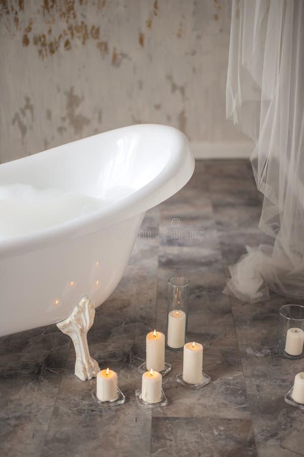 Świeczki kłama na podłoga obok balii z pianą zdjęcia royalty free
