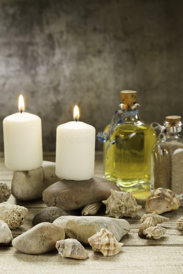 Świeczki pali na rzecznych otoczakach z seashells i istotnym oleju na drewno stole i unfocused popielatym tle zdjęcie royalty free