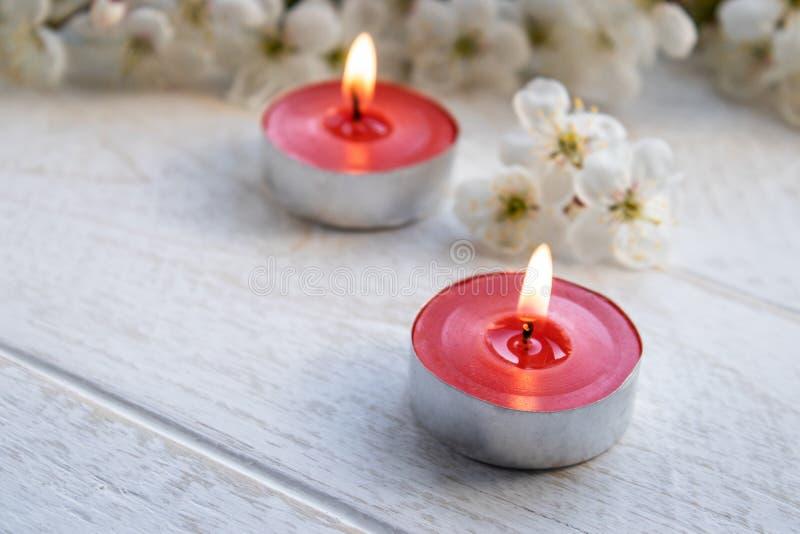 Świeczki stojaki na drewnianym bielu stole blisko gałąź biali kwiaty wiśnia zdjęcia stock