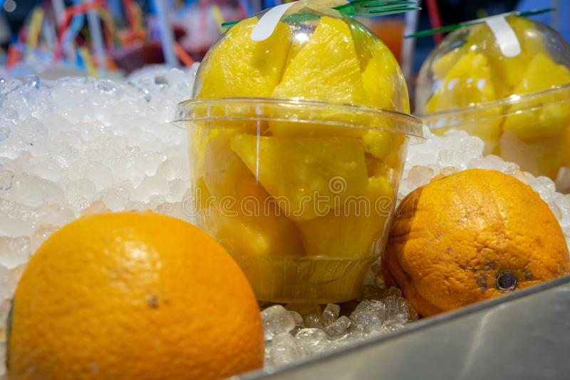 Świezi ananasów kawałki w plastikowych przejrzystych filiżankach i pomarańczach na lodzie dla sprzedaży przy rolnikami wprowadzać fotografia stock