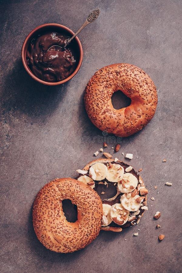 Świezi bagels z czekoladową śmietanką, bananem i dokrętkami na ciemnym nieociosanym tle, Wyśmienicie słodki śniadaniowy Odgórny w fotografia royalty free