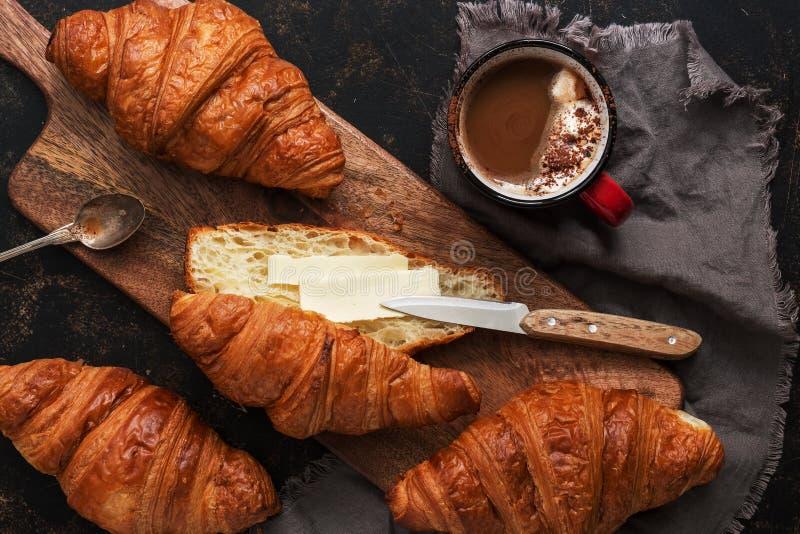 Świezi croissants z masłem i gorącą kawą na tnącej drewnianej desce, ciemny nieociosany tło Odgórny widok, mieszkanie nieatutowy obraz stock