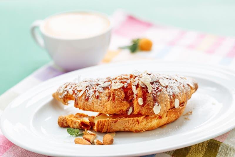 Świezi croissants zakrywający z dżemem i pokrojonym migdałem na zamazanym coffe filiżanki tle dla śniadania zdjęcie royalty free