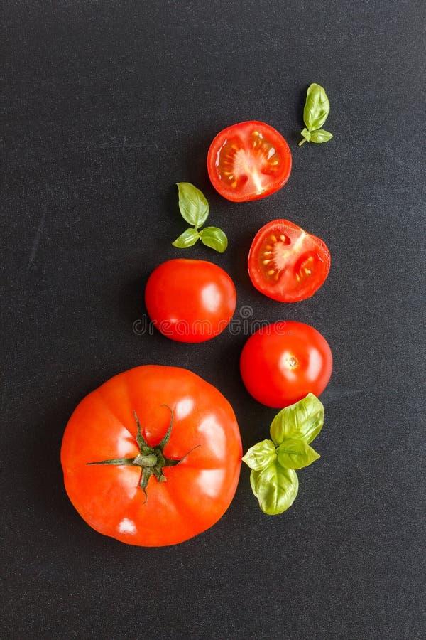 Świezi czereśniowi pomidory na czarnym chalkboard tle z ziele obraz stock