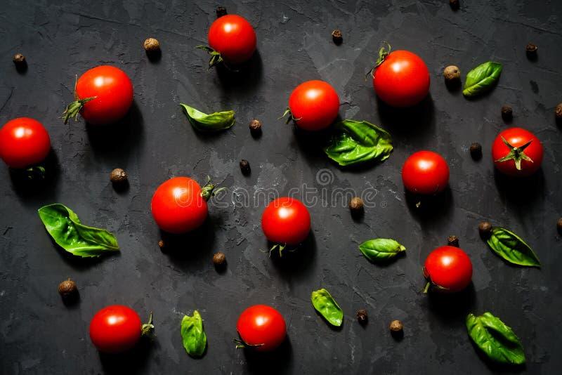 Świezi czereśniowi pomidory z basilów liśćmi i czarnym pieprzem na czarnym kamienia stole, warzywo wzór, odgórny widok obraz stock