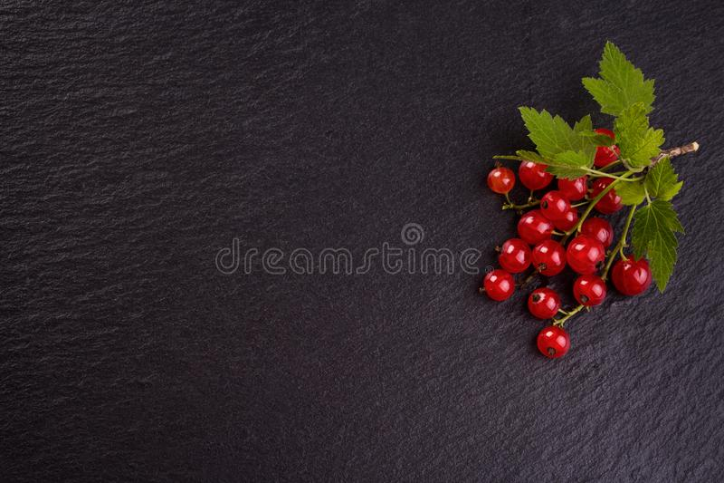 Świezi czerwoni rodzynki na czerń łupku tle fotografia stock